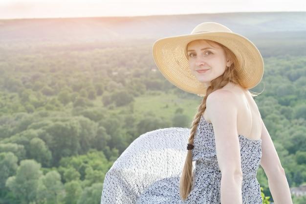 Mooi meisje in hoed en jurk zit op bos