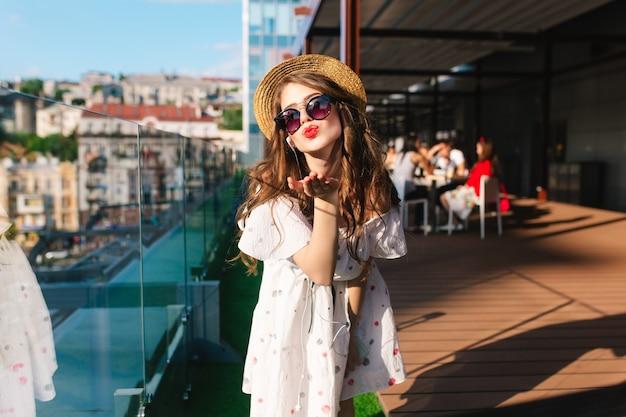 Mooi meisje in hoed met lang haar luistert naar muziek via een koptelefoon op het terras. ze draagt een witte jurk met blote schouders, zonnebril, rode lippenstift. ze stuurt een kus naar de camera.