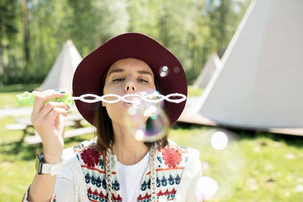 Mooi meisje in hoed zeepbellen blazen door stok tijdens het weekend doorbrengen op festival camping