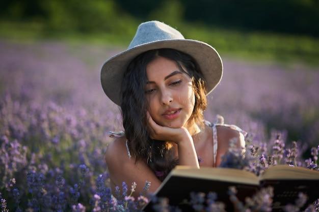 Mooi meisje in hoed zittend in paarse lavendel veld en lees boek.