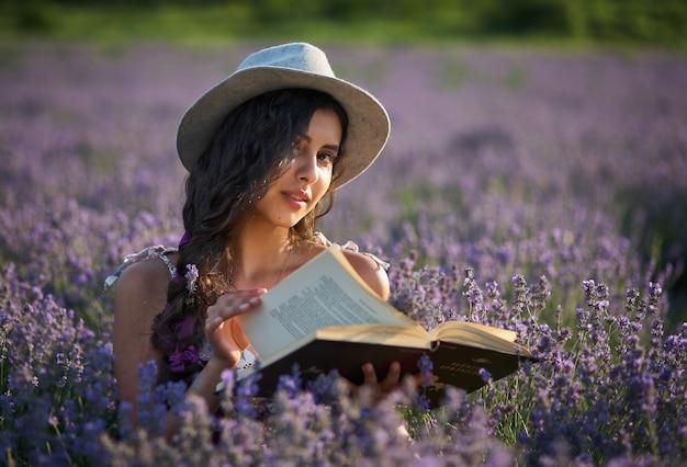Mooi meisje in hoedenzitting op paars lavendelgebied en het lezen van een boek.