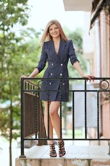 Mooi meisje in jas-jurk op balkon