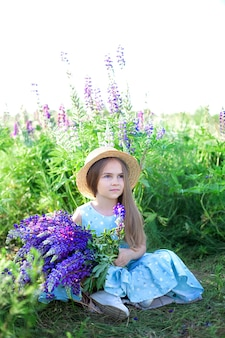 Mooi meisje in jurk en hoed op gebied van lupinen