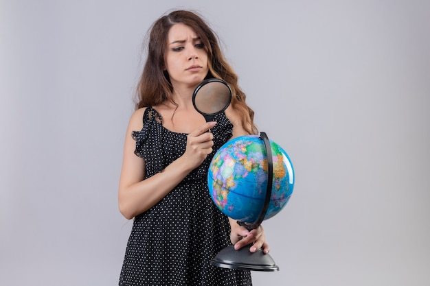 Mooi meisje in jurk in polka dot globe kijken door vergrootglas met ernstig gezicht staande op witte achtergrond