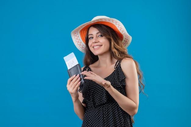 Mooi meisje in jurk in polka dot in zomer hoed bedrijf vliegtickets presenteren met arm van haar hand glimlachend vrolijk positief en gelukkig permanent over blauwe achtergrond