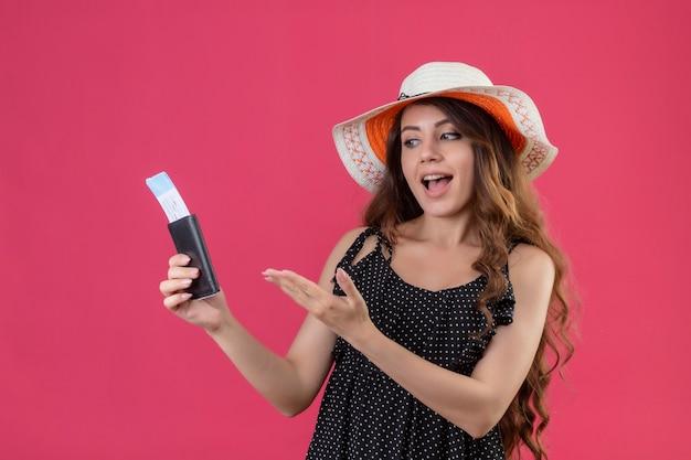 Mooi meisje in jurk in polka dot in zomer hoed bedrijf vliegtickets presenteren met arm van haar hand glimlachend vrolijk positief en gelukkig permanent over roze achtergrond