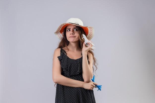 Mooi meisje in jurk in polka dot in zomer hoed houden speelgoed vliegtuigen opzij kijken ontevreden met sceptische uitdrukking op gezicht staande op witte achtergrond