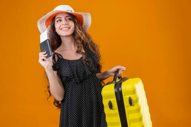 Mooi meisje in jurk in polka dot in zomer hoed met vliegtickets en koffer opzij kijken met blij gezicht glimlachend vrolijk permanent over gele achtergrond