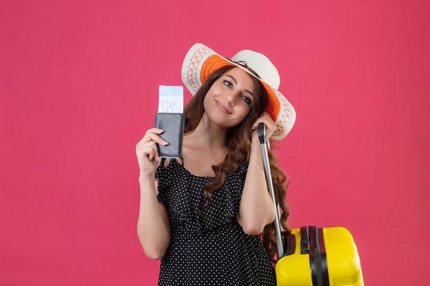 Mooi meisje in jurk in polka dot in zomer hoed permanent met koffer bedrijf vliegtickets kijken camera glimlachend vriendelijk over roze achtergrond