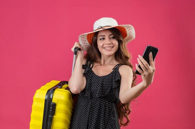 Mooi meisje in jurk in polka dot in zomer hoed permanent met koffer kijken naar scherm van haar mobiele telefoon glimlachend vrolijk op roze achtergrond