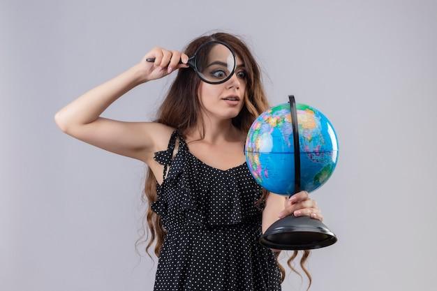 Mooi meisje in jurk in polka dot kijken naar globe door vergrootglas geïntrigeerd staande op witte achtergrond