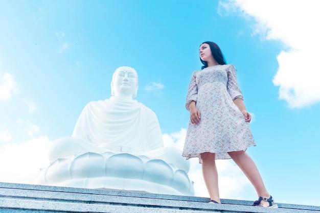 Mooi meisje in jurk staande in de buurt van een monument voor boeddha.