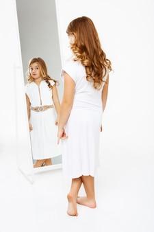 Mooi meisje in jurk staande voor spiegel.