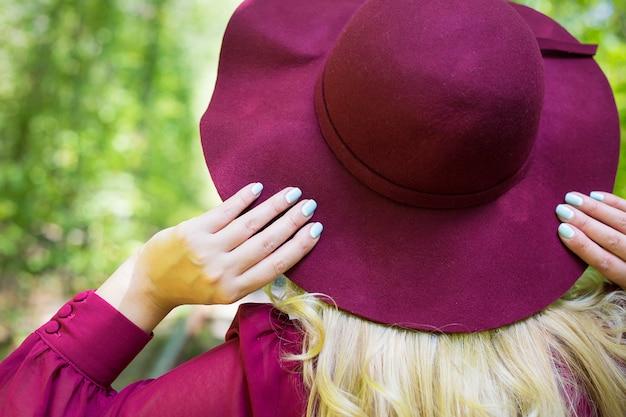 Mooi meisje in kersenjurk met een hoed in bos