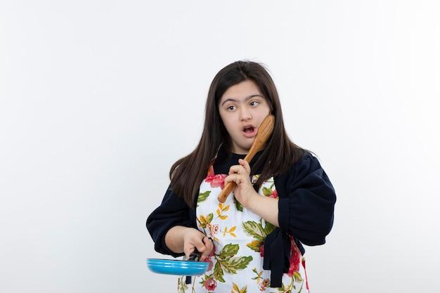 Mooi meisje in kleurrijke schort klaar om te koken met lepel en pan.