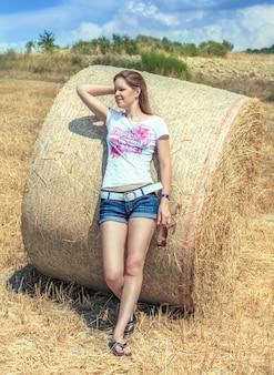 Mooi meisje in korte broek staande in een veld op basis van een ronde baal hooi
