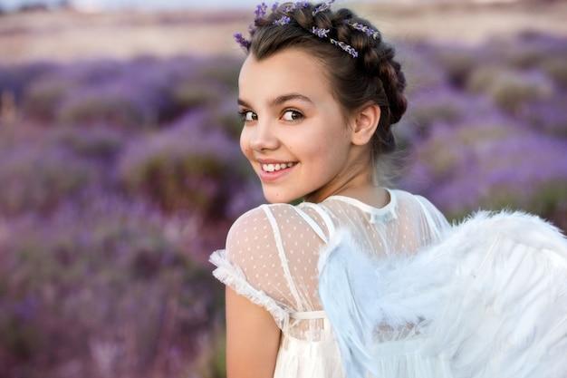 Mooi meisje in lavendel krans en retro jurk op het veld lavendel. engel. mooi meisje op het lavendelgebied op zonsondergang in frankrijk. meisje verzamelt lavendel.