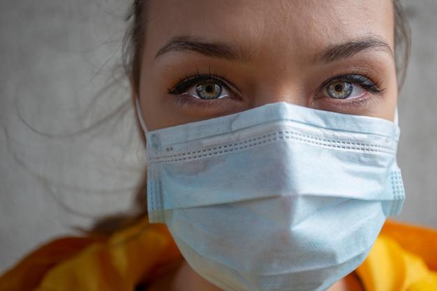 Mooi meisje in medisch masker in een geïsoleerd verlaten in quarantaine geplaatst gebouw