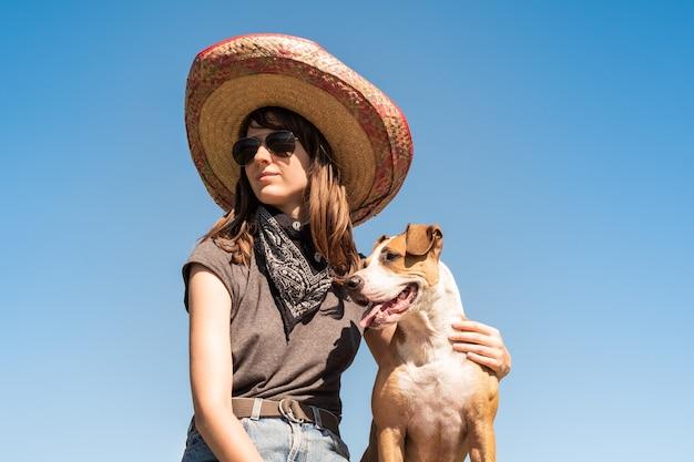 Mooi meisje in mexicaanse hoed verkleed als bandiet van gangster met hond in coole zonnebril. vrouwelijke persoon in sombrerohoed en bandana poseren met puppy als feestelijk symbool van mexico of voor halloween
