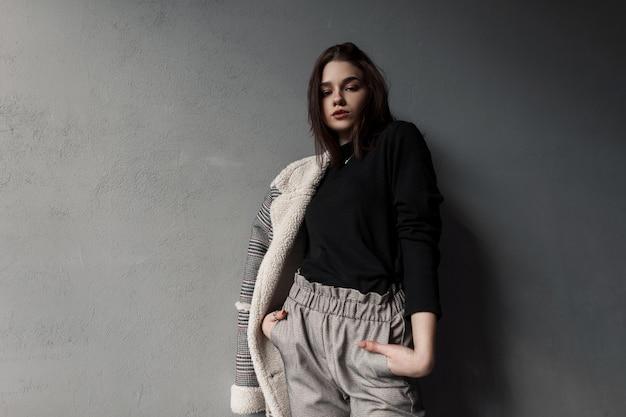 Mooi meisje in mode-uitloper staat in de buurt van grijze muur