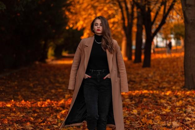 Mooi meisje in modieuze kleding loopt in een herfstpark met gekleurd gebladerte bij zonsondergang