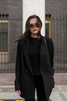 Mooi meisje in modieuze zwarte casual jeugdkleding. moderne jonge vrouw in modieuze blazer in stijlvol zwart t-shirt staat op straat in de stad. mooie zwarte outfit voor dames. Premium Foto