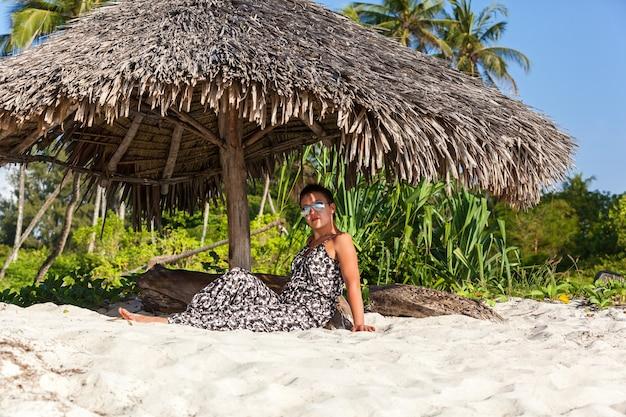 Mooi meisje in overall en zonnebril, zit onder een parasol met stok op het strand met hoge palmbomen en wit zand. afrika mombasa kust van de indische oceaan