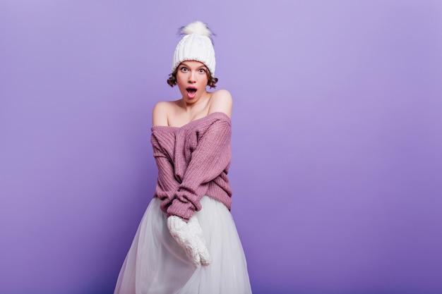 Mooi meisje in paarse trui verbazing uiten geïsoleerd op heldere muur. verrast kortharige brunette vrouw in witte rok staan