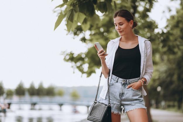 Mooi meisje in park met behulp van de telefoon