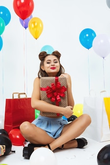 Mooi meisje in pin-up kleding zwaaiende kus op zoek recht