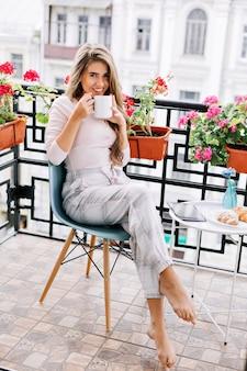 Mooi meisje in pyjama die 's ochtends op het balkon ontbijten. ze drinkt tee en glimlacht.