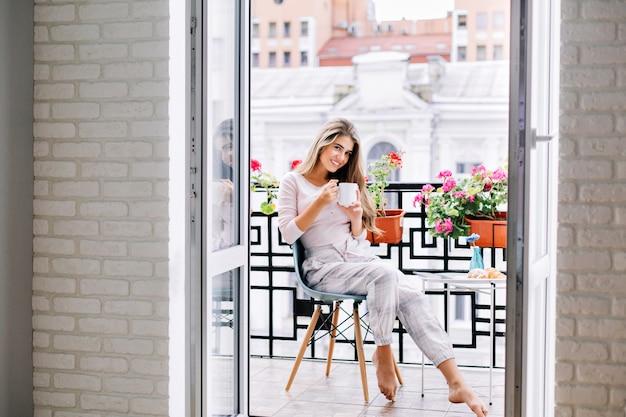 Mooi meisje in pyjama's ontbijten op balkon thuis in de ochtend. ze houdt een kopje vast en glimlacht.