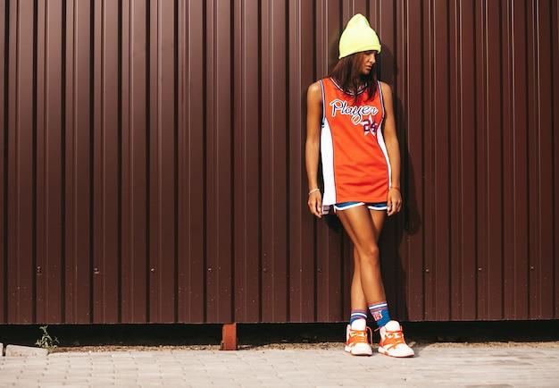 Mooi meisje in rode basketbalsporten die dichtbij bruine metaalmuur stellen