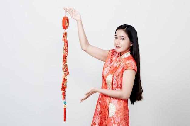 Mooi meisje in rode cheongsam die voetzoekers houden