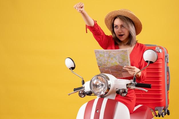 Mooi meisje in rode jurk op bromfiets met grote koffer met kaart