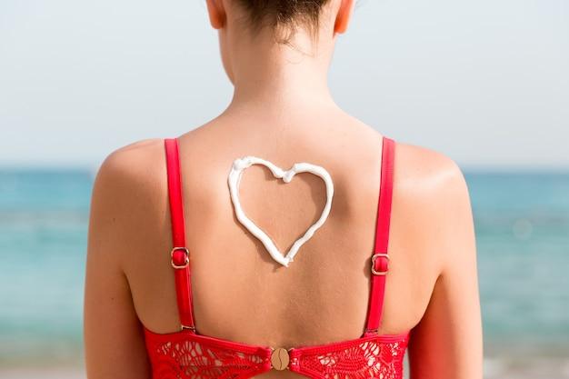 Mooi meisje in rode zwembroek heeft sunblock in de vorm van een hart aan de achterkant op het strand.