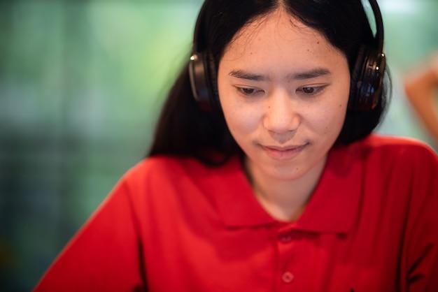 Mooi meisje in rood shirt met koptelefoon, luister naar muziek, werk vanuit huis, binnen thuis, stedelijk lifestyle concept, close-up portret op gezicht, aziatische jongedame die online werkt.