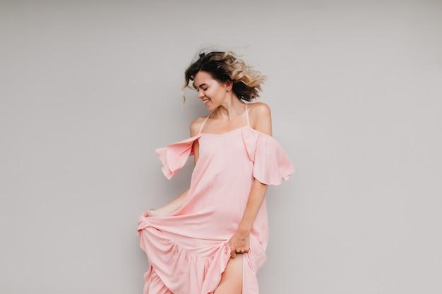 Mooi meisje in roze jurk dansen met blij gezicht expressie. portret van vrolijk vrouwelijk model dat echte positieve emoties uitdrukt.