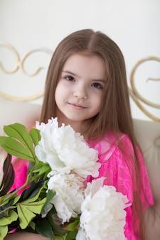 Mooi meisje in roze jurk met witte pioenrozen