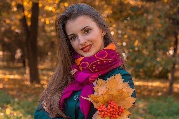 Mooi meisje in roze sjaal glimlacht en houdt bladeren en rowan in de hand close-up