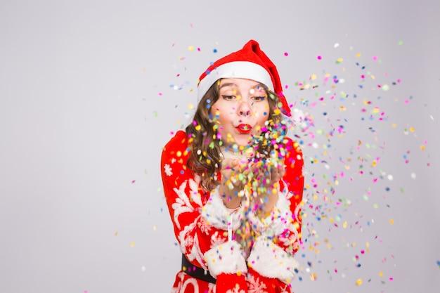 Mooi meisje in santa's kostuum verwelkomen het nieuwe jaar confetti blazen naar de camera. nieuwjaarsviering en partijconcept.