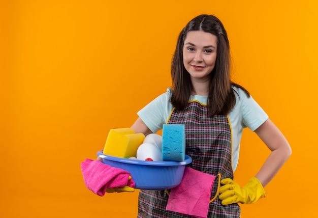 Mooi meisje in schort en rubberen handschoenen bekken met reinigingsgereedschap glimlachend vriendelijk camera kijken te houden