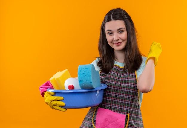 Mooi meisje in schort en rubberen handschoenen bekken met schoonmaak tools glimlachend vriendelijk kijken camera terug wijzend houden