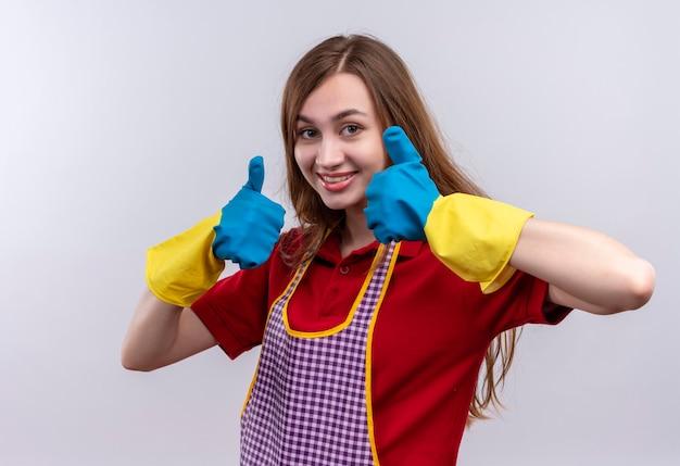 Mooi meisje in schort en rubberen handschoenen glimlachend duimen opdagen met beide handen