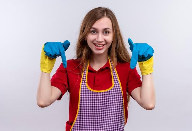 Mooi meisje in schort en rubberen handschoenen glimlachend wijzend met vingers naar beneden