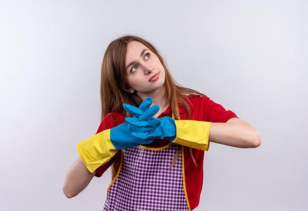 Mooi meisje in schort en rubberen handschoenen hand in hand samen op zoek opzij met peinzende uitdrukking