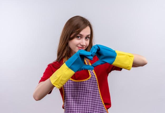 Mooi meisje in schort en rubberen handschoenen hart gebaar met vingers over borst glimlachen