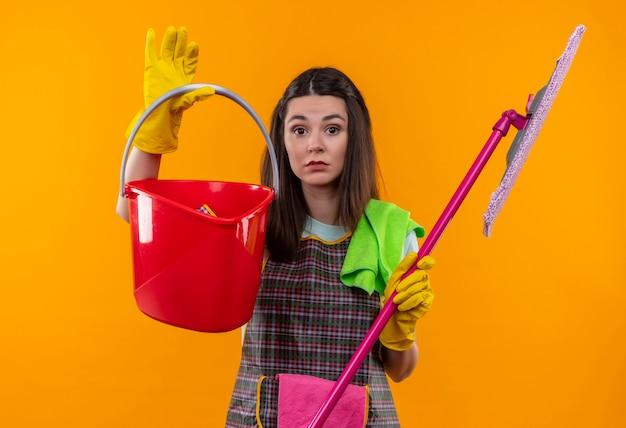 Mooi meisje in schort en rubberen handschoenen met emmers en dweil op zoek verward