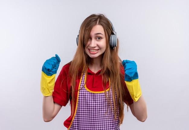 Mooi meisje in schort en rubberen handschoenen met koptelefoon op hoofd balde vuisten gek gelukkig