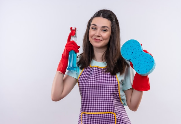 Mooi meisje in schort en rubberen handschoenen met schoonmaak spray en spons camera kijken met blij gezicht lachend